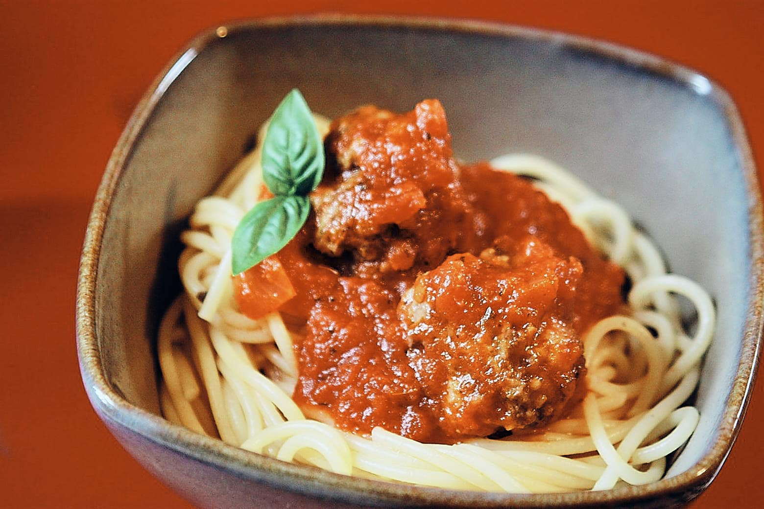 Spaghetti and meatballs in a bowl with tomato sauce and basil.