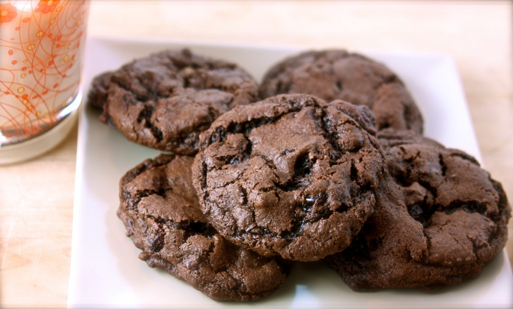 Chocolate cookies on a white plate with a glass of milk.
