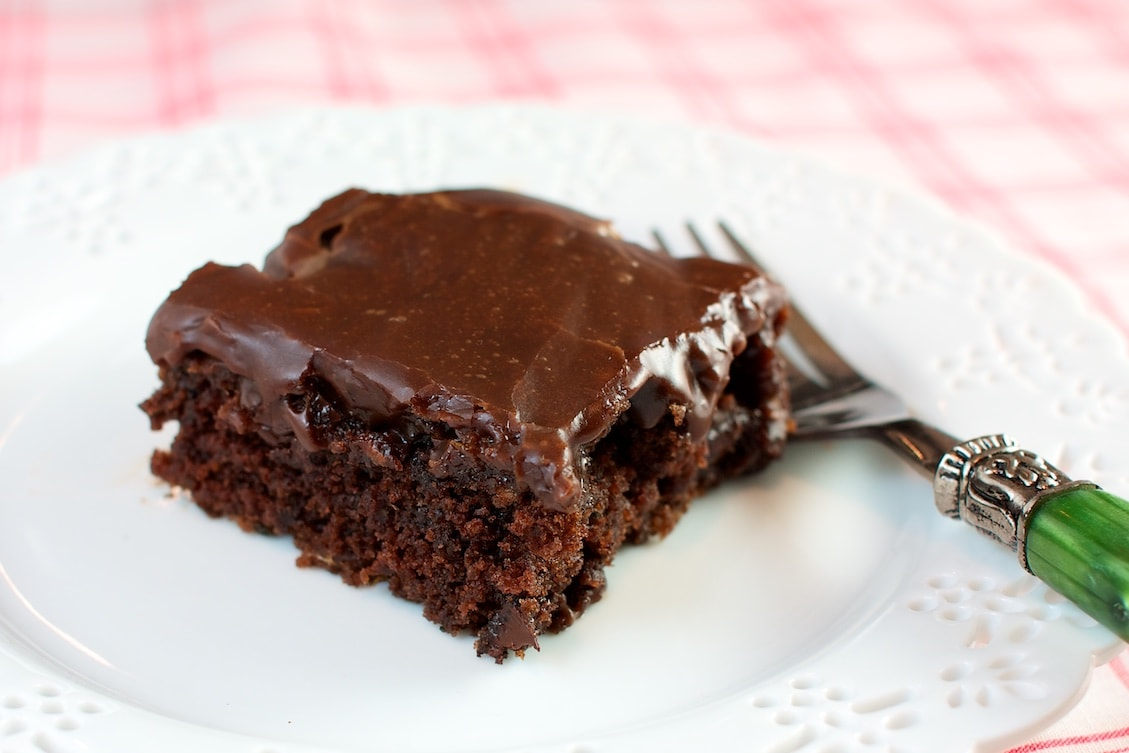 A slice of chocolate sheet cake on a white plate.