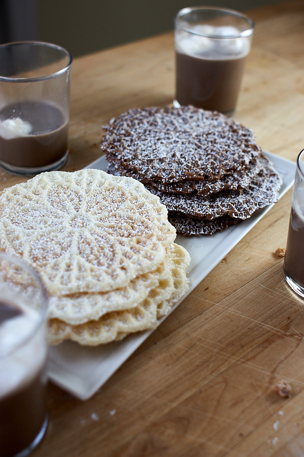 Vanilla and chocolate pizzelle cookies on a tray with glasses of chocolate milk