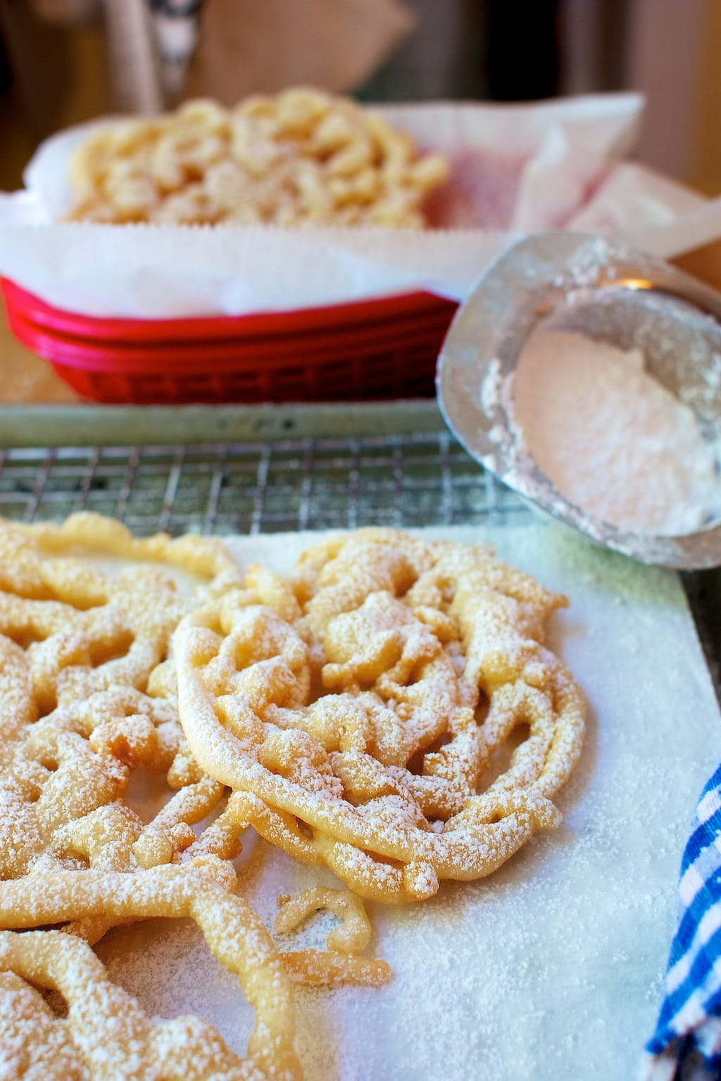 Funnel cakes cooling on a tray with powdered sugar.