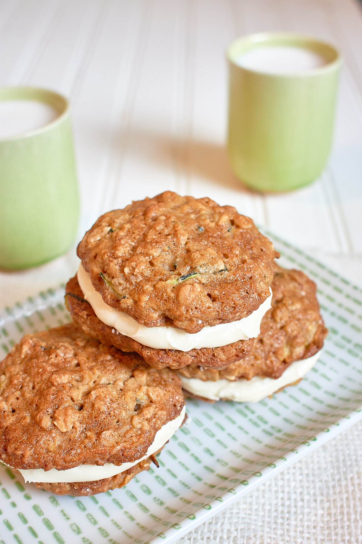 3 zucchini sandwich cookies on plate with 2 glasses of milk