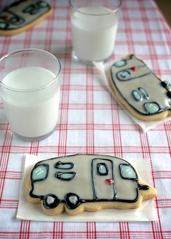 A camper sugar cookie on a gingham tablecloth with a glass of milk