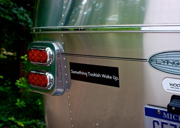 "An Airstream Camper with a bumper sticker that reads ""Something Tookish Woke Up."""