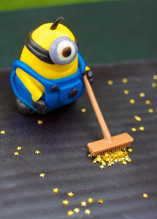 A fondant Minion character sweeping stars.