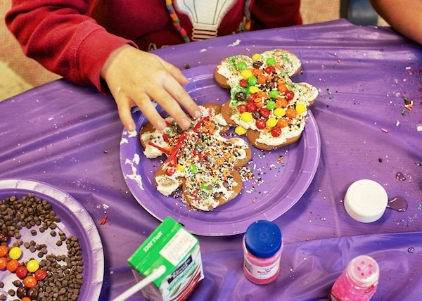 Kids decorating gingerbread men with candy and frosting.