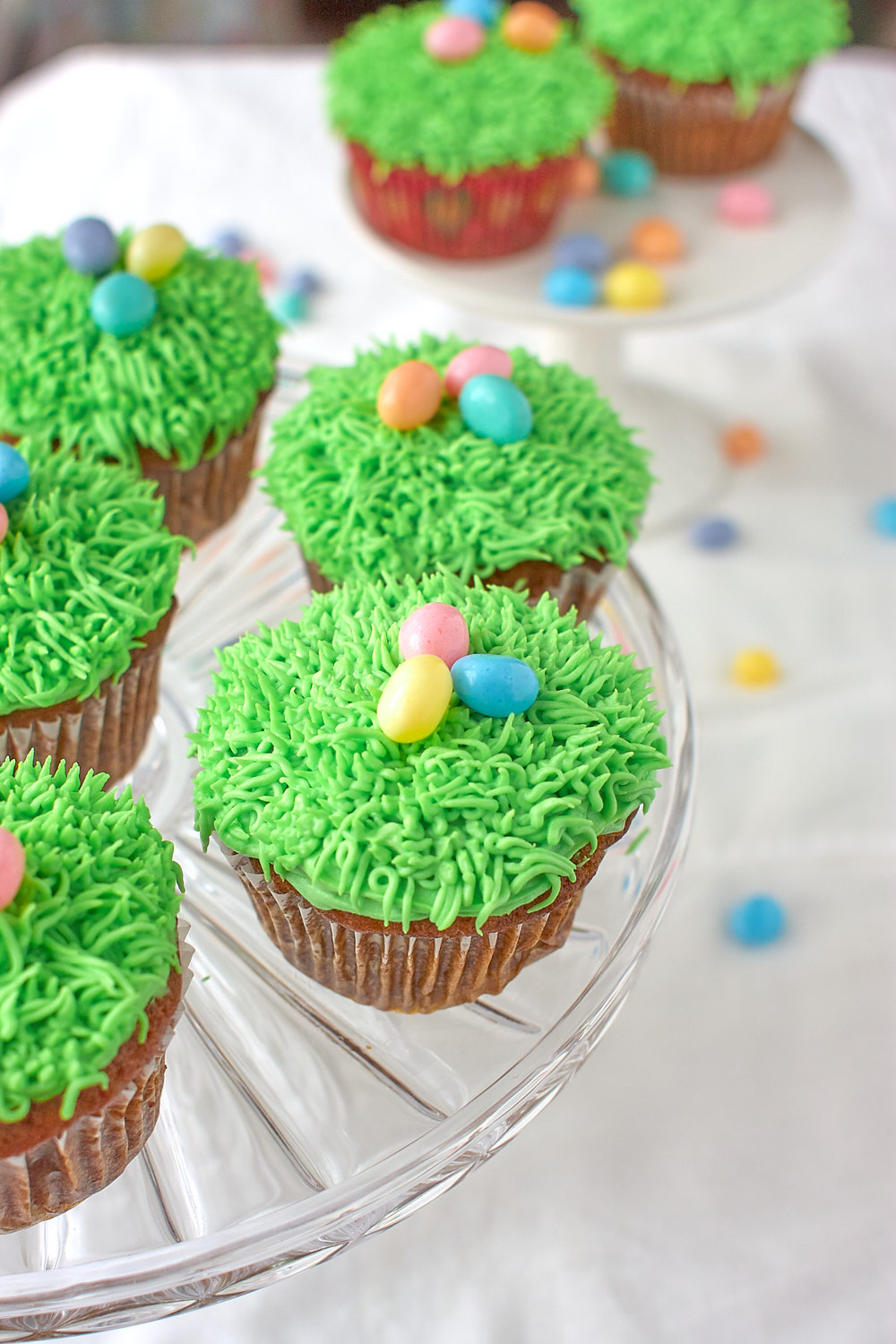 Carrot cupcakes with green grass frosting and jellybeans on a cake stand.
