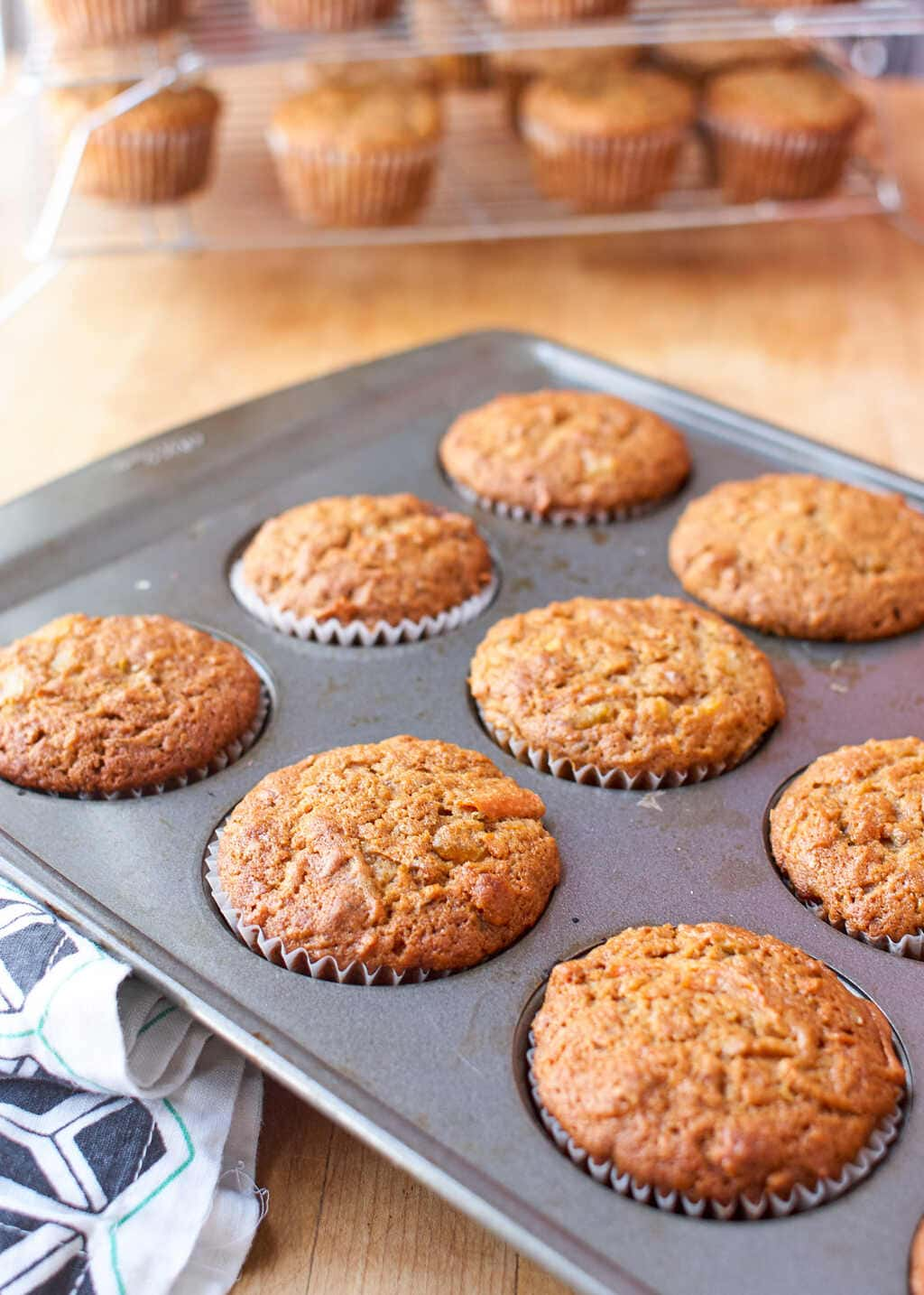 Baked carrot cupcakes in a muffin pan.