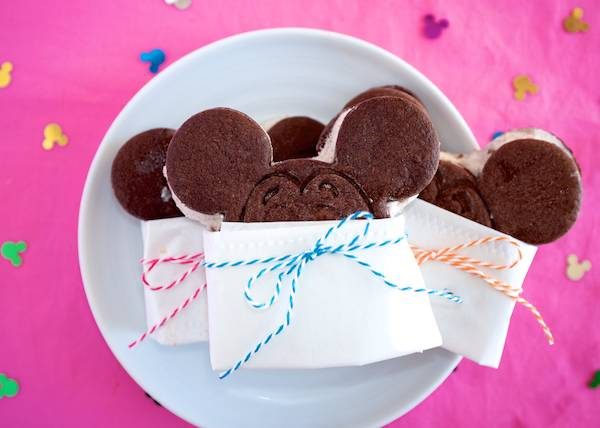 Mickey Mouse shaped ice cream sandwiches wrapped in paper with colorful twine.