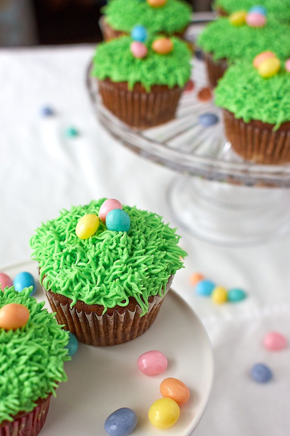 Carrot cupcakes with green grass frosting and jellybeans on a stand.