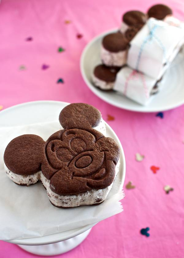 Mickey shaped ice cream sandwiches on a stand.