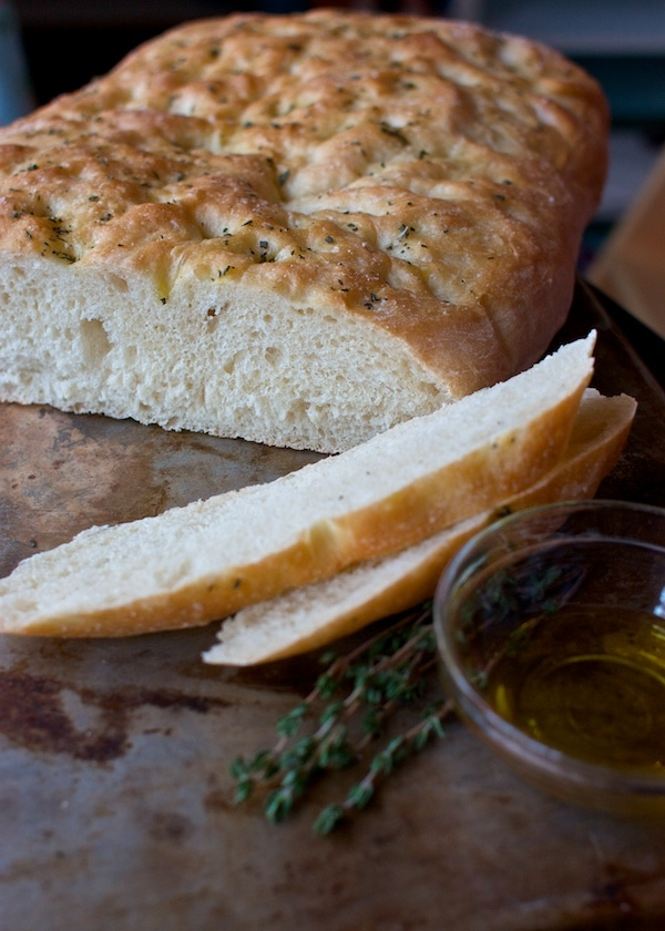 A loaf of fresh focaccia cut into slices with oil and herbs.
