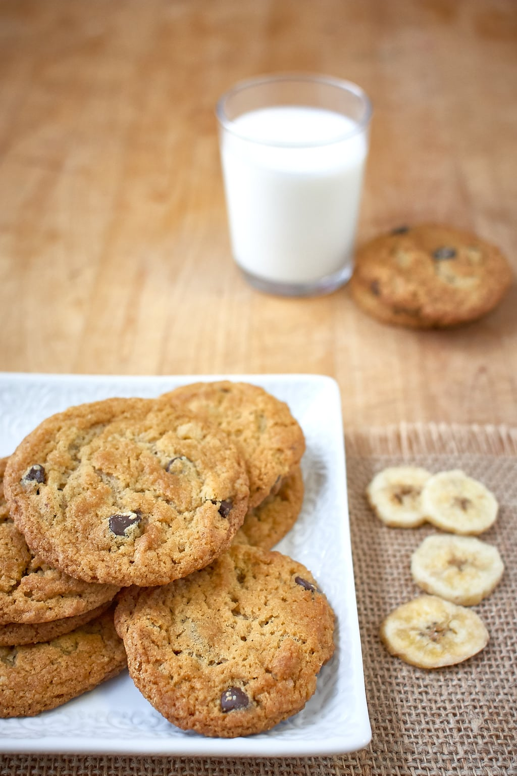 Chocolate chip cookies on plate with banana chips and milk.