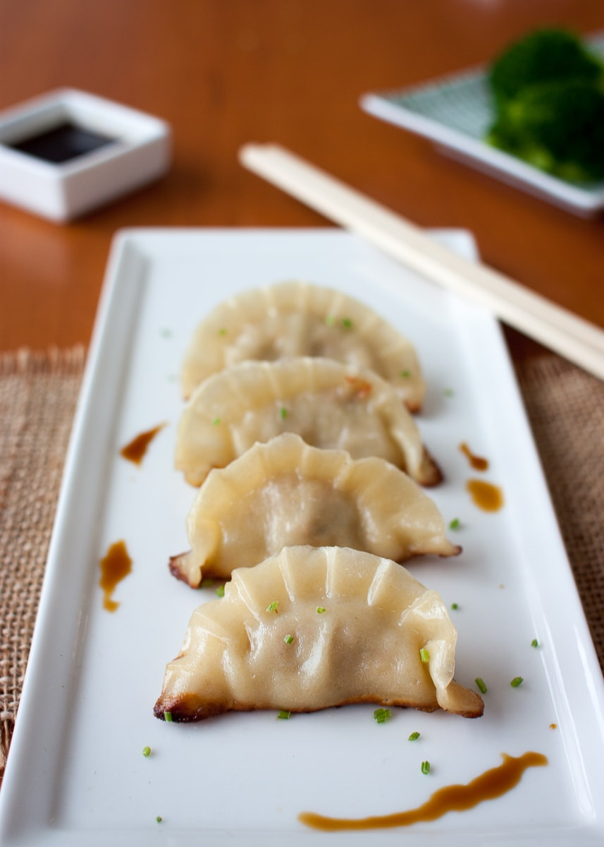 Chinese dumplings on a white plate with chopsticks and soy sauce