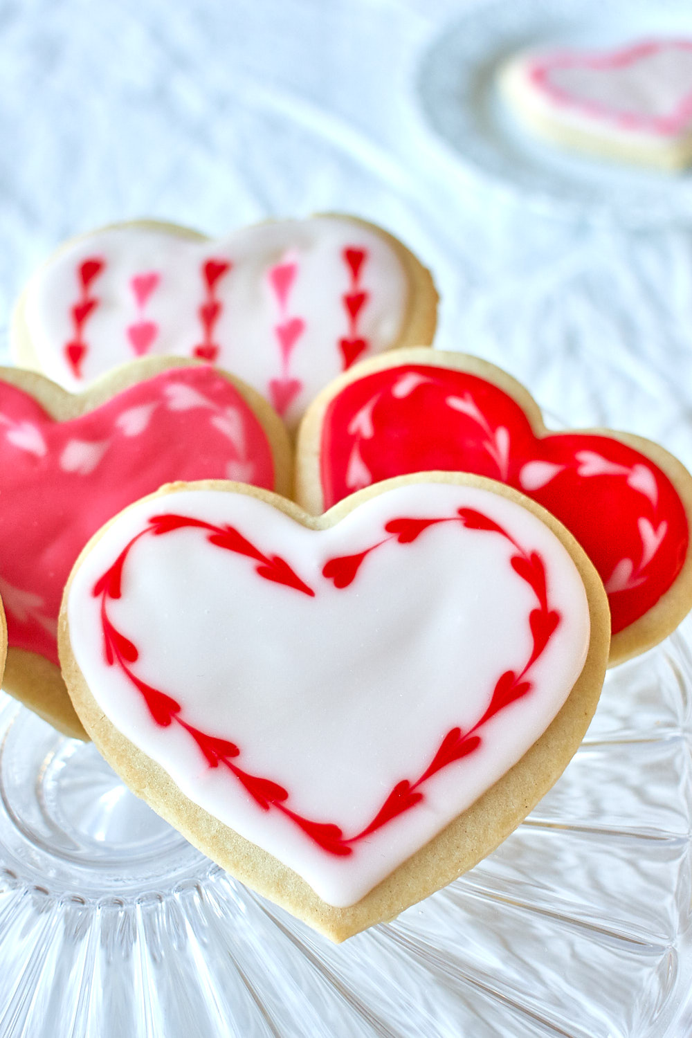 Red and white heart shaped sugar cookies on a plate