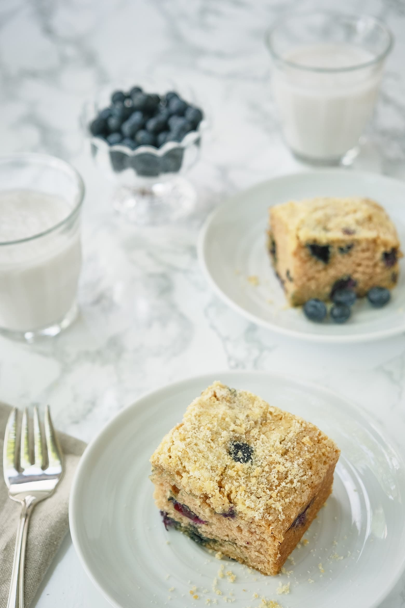 Two pieces  of blueberry boy bait crumbcake on a plate with a fork.