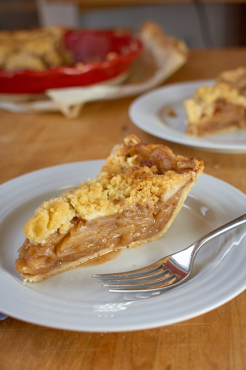 A slice of Dutch Apple Pie on a plate with a fork.