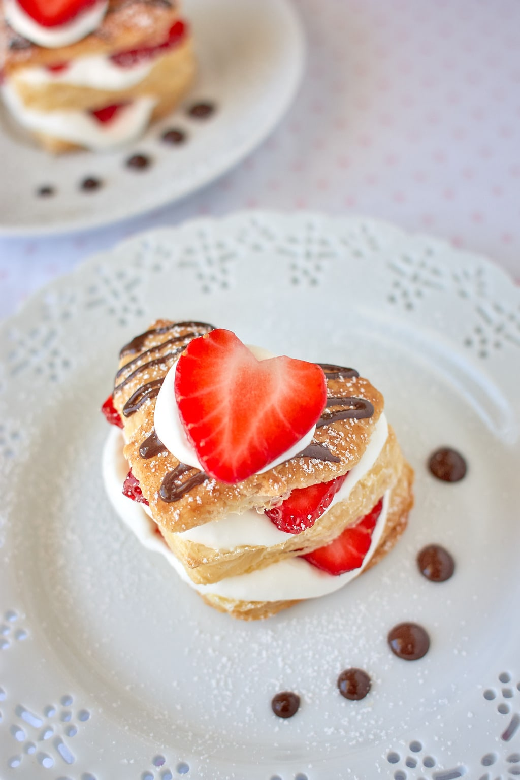 Heart shaped strawberry napoleon dessert with chocolate sauce, strawberries, and whipped cream on a plate.