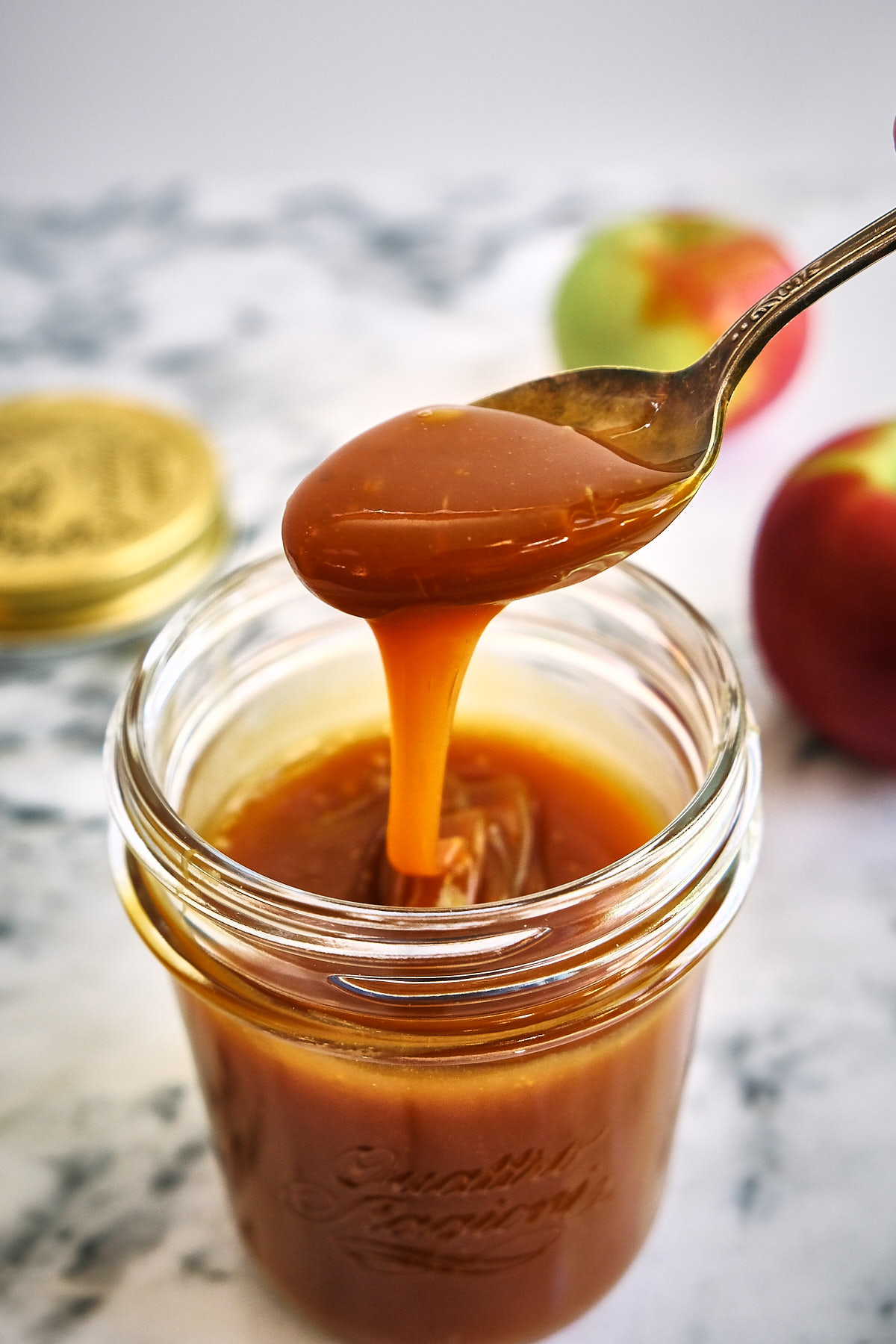 A spoonful of dairy free caramel apple dip from a mason jar with apples on the table.
