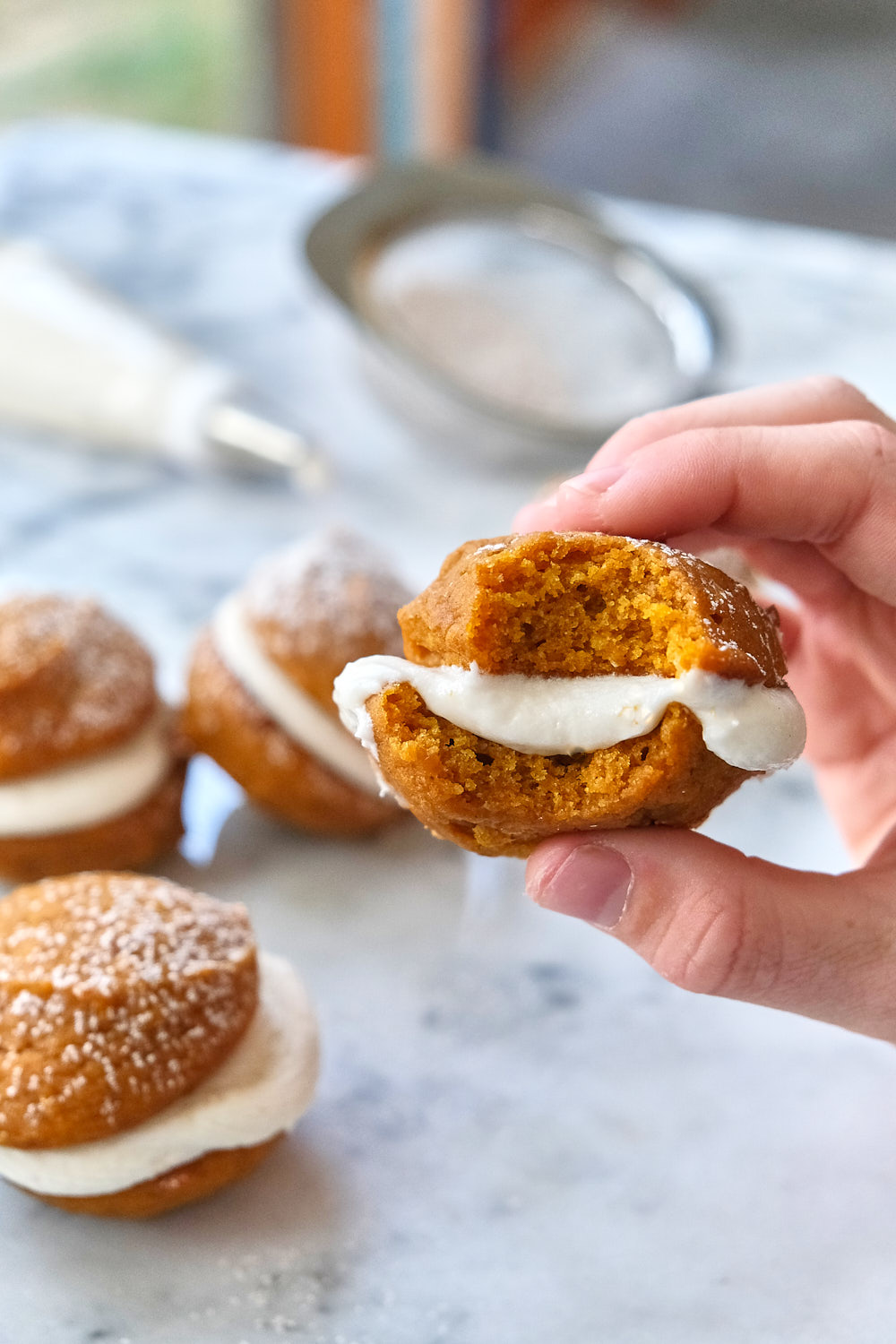 Mini pumpkin whoopie pie with a bite taken out of it.