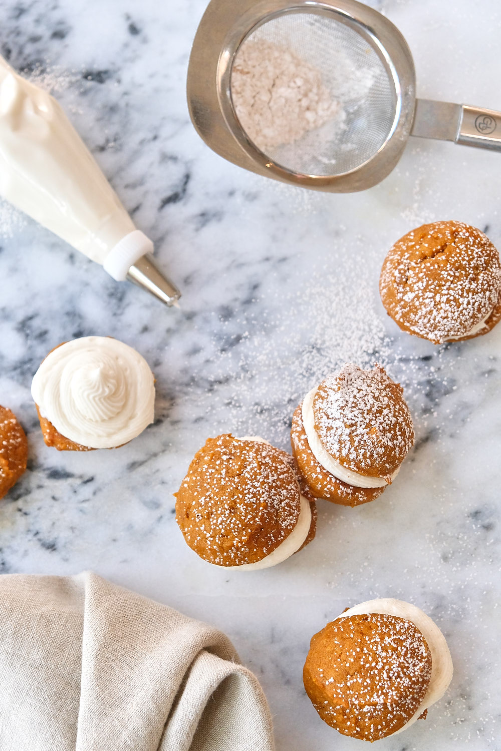 Mini pumpkin whoopie pies on table with a dusting of spices and powdered sugar.