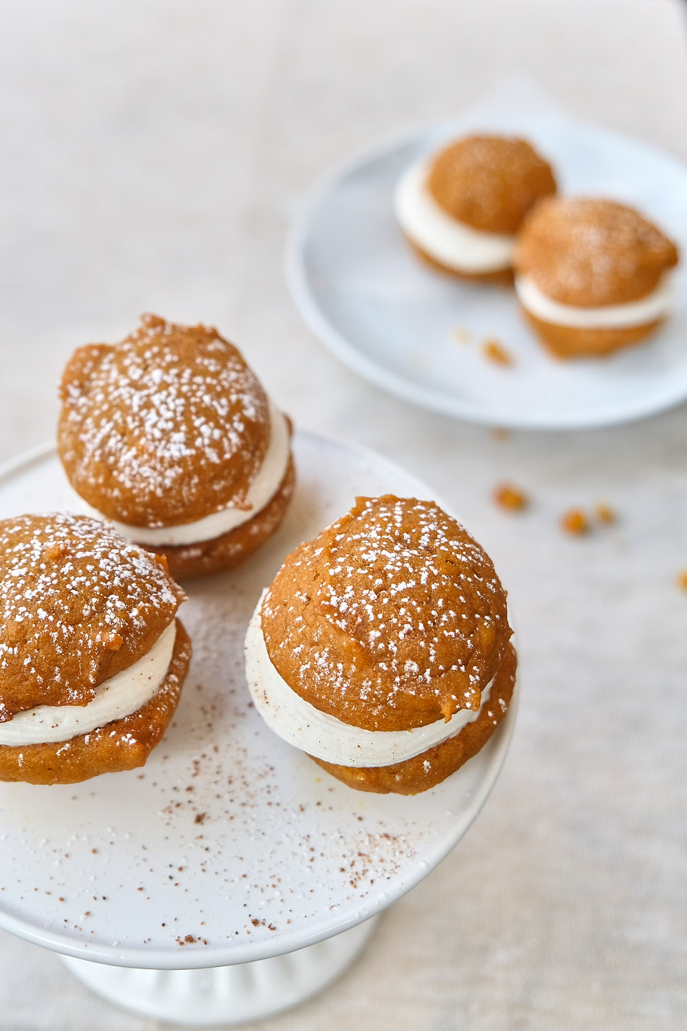 Mini pumpkin whoopie pies on a cake stand with a dusting of spices and powdered sugar.