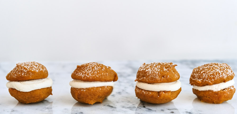 A row of four pumpkin whoopie pies on a marble countertop.