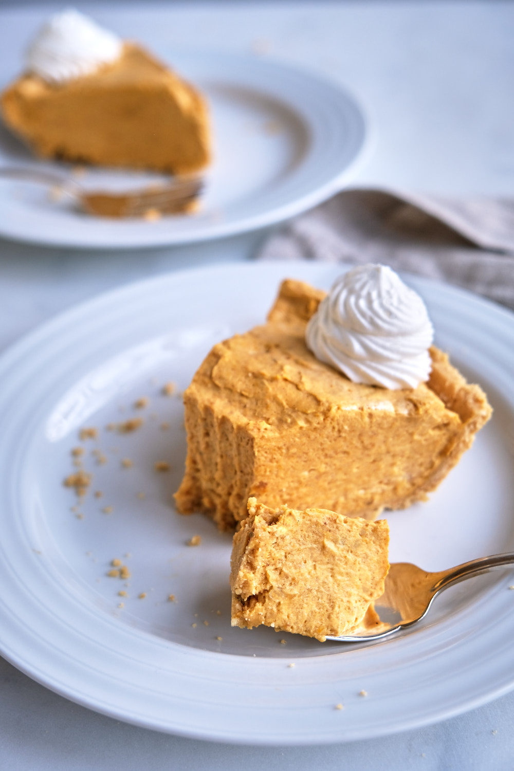 A slice of pumpkin cream pie on a plate with a bite on a fork.
