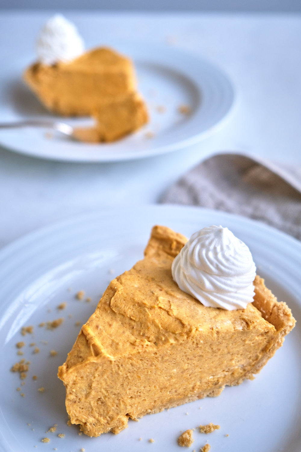 A slice of pumpkin cream pie on a plate with whipped cream.