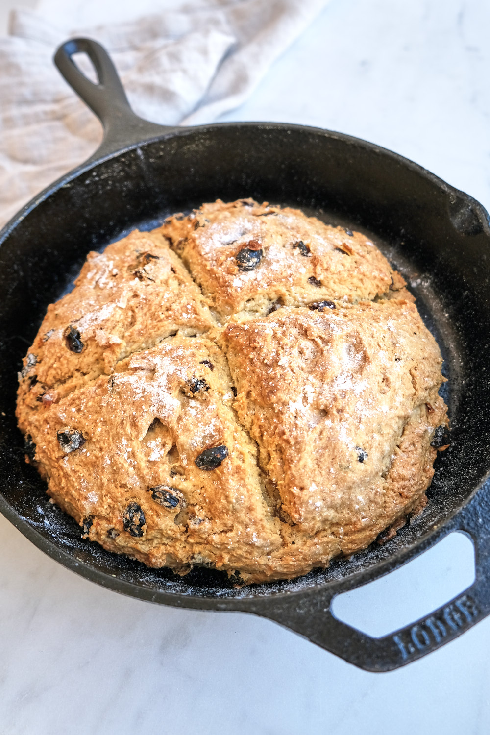 A loaf of irish soda bread in an iron skillet