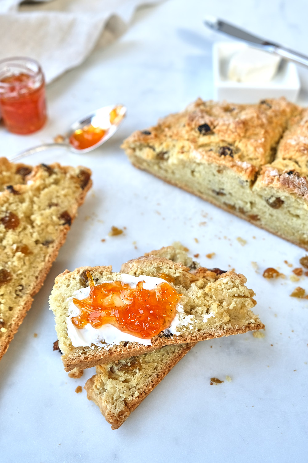 A loaf of irish soda bread cut into slices with orange marmalade.