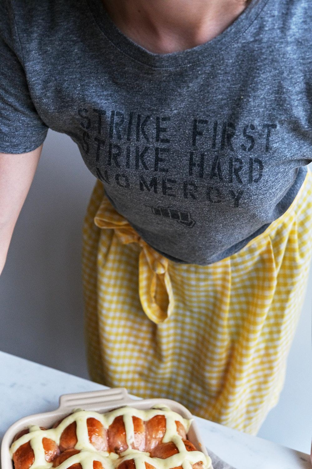 A girl in a t shirt with a yellow gingham apron and a pan of hot cross buns.