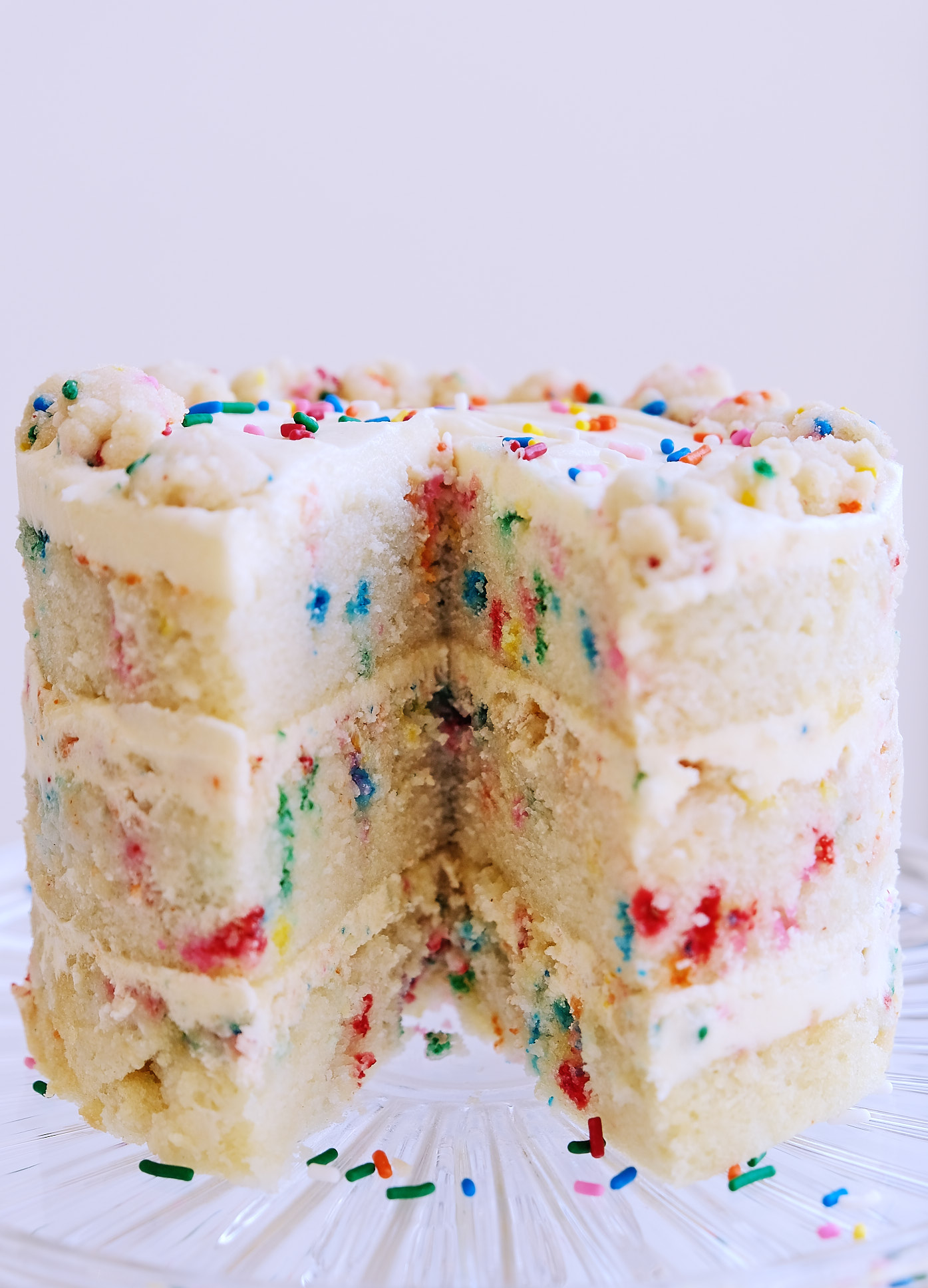 A side view of a dairy-free egg-free Milk Bar Birthday Cake on a cake stand.