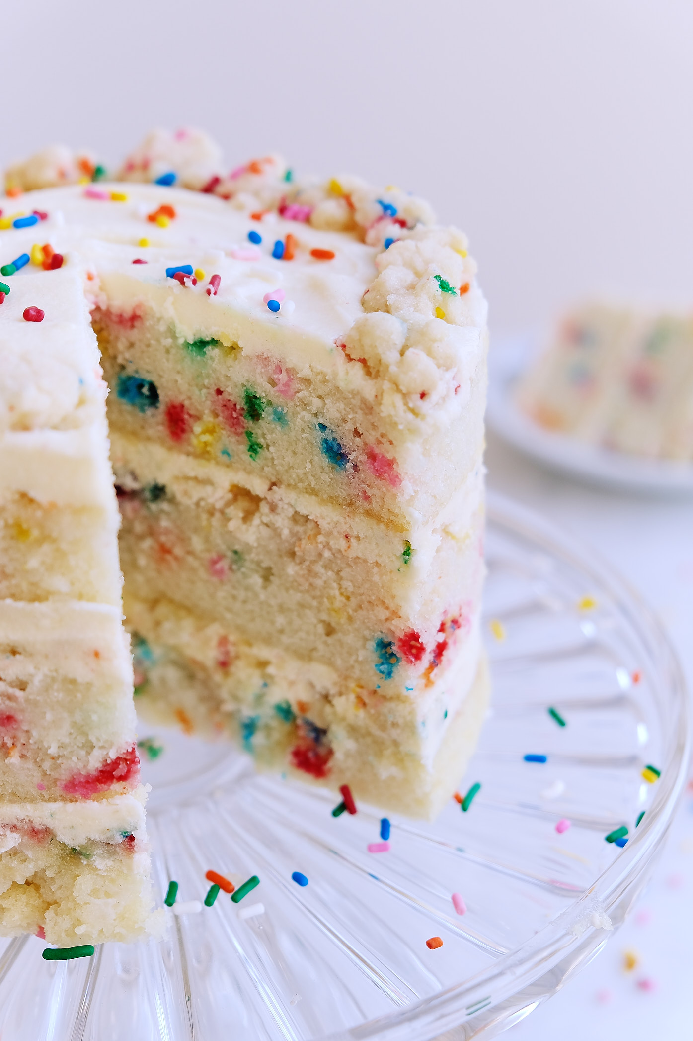 A side view inside a dairy-free egg-free Milk Bar Birthday Cake on a cake stand.