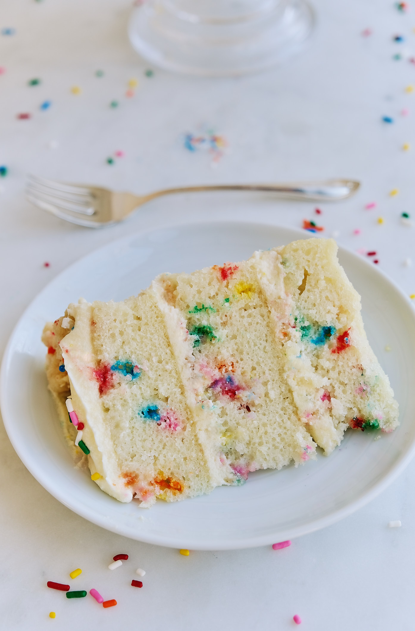 A slice of dairy-free egg-free Milk Bar Birthday Cake on a plate with a fork.