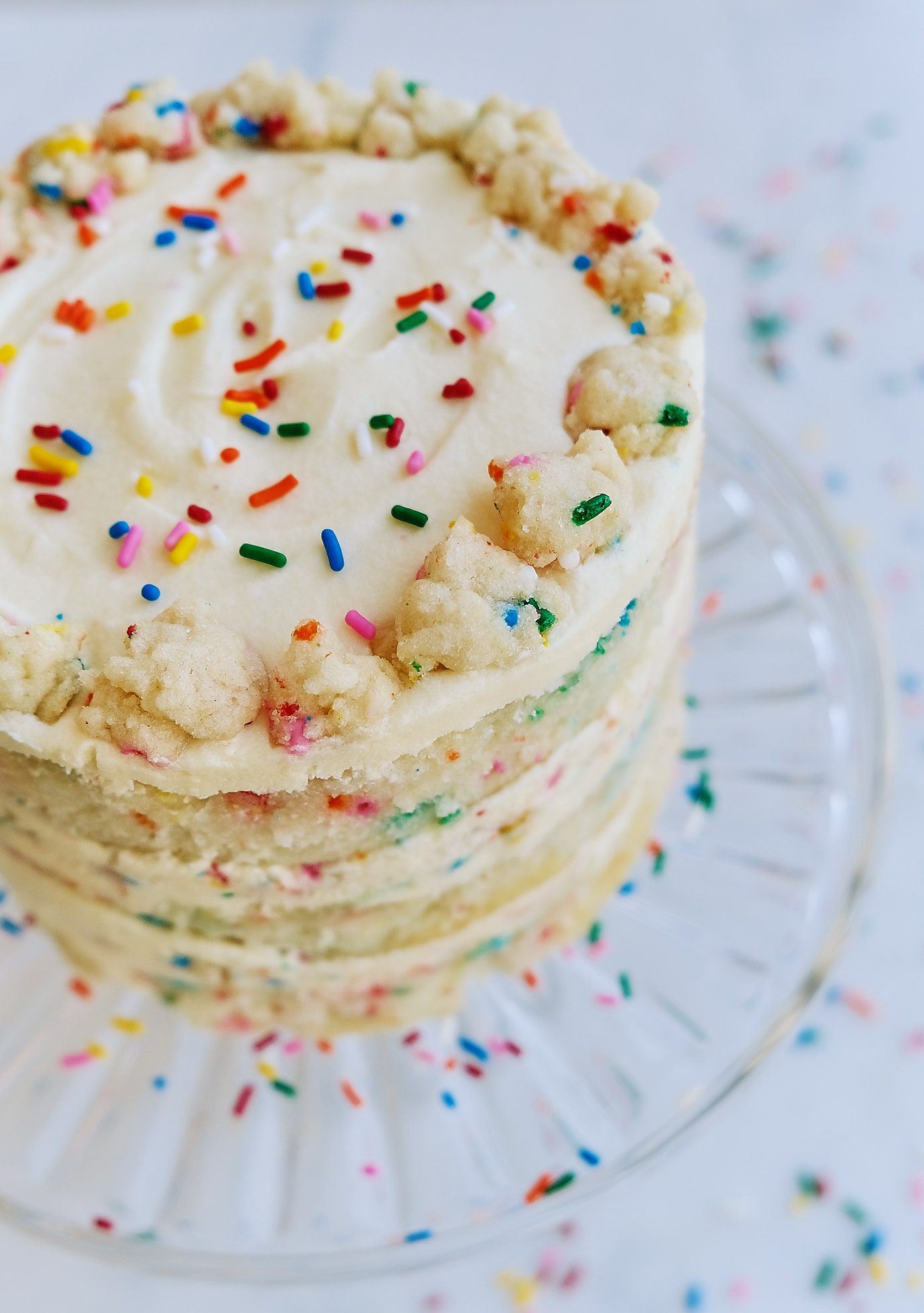 A top view of a dairy-free egg-free Milk Bar Birthday Cake on a cake stand.